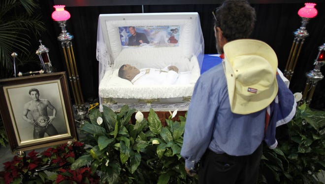 """A man stands in front of the open casket of former boxing champion Hector """"Macho"""" Camacho during a memorial in San Juan, Puerto Rico, on Tuesday."""
