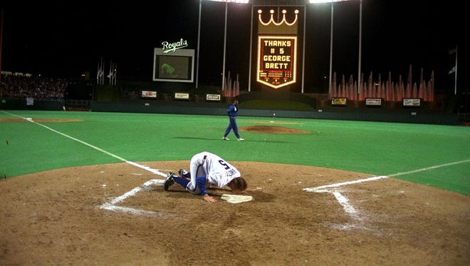 Kansas City Royals' George Brett kisses home plate at Kauffman Stadium after the last home game of his career September 29, 1993 in Kansas City, MO.