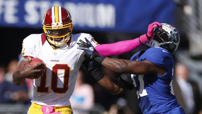 Washington Redskins quarterback Robert Griffin III (10) strong arms New York Giants strong safety Kenny Phillips (21) during a 2012 game.