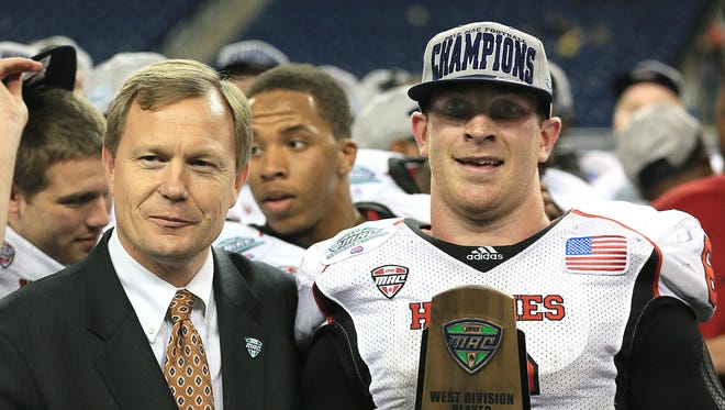 Northern Illinois quarterback Jordan Lynch holds the MAC championship trophy after Friday night's win over Kent State.