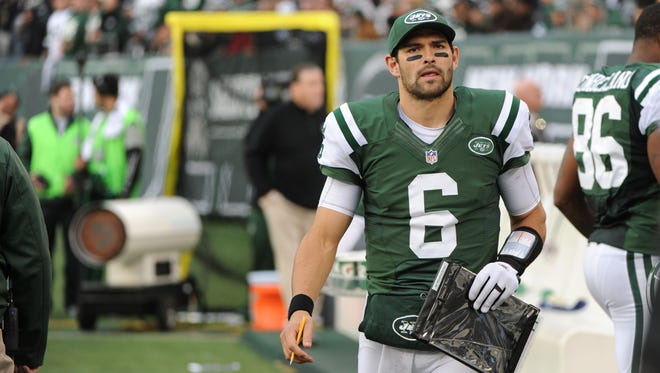New York Jets quarterback Mark Sanchez (6) holds a clipboard while on the bench during the second half of an NFL football game against the Arizona Cardinals.