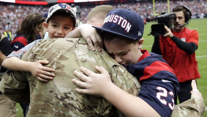 United States Army Chief Warrant Officer Eric Spoerle, center, is hugged by his sons Tristin, right, and Brandon.