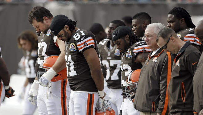 Cleveland Browns offensive tackle Joe Thomas, left, tight end Alex Smith (81),and running back Trent Richardson (33)  join their teammates in a moment of silence for the victims of the Connecticut school shootings.
