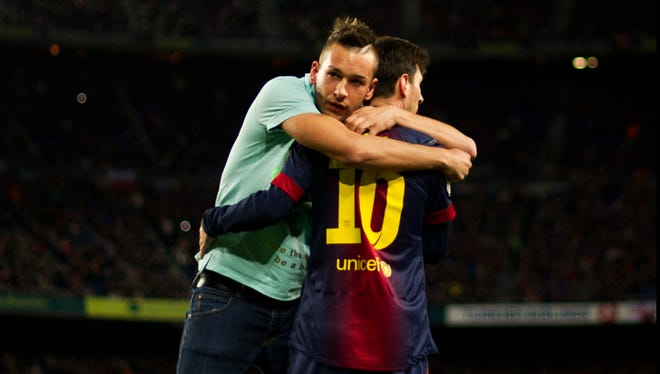 Messi shares a moment with a pitch invader at Camp Nou stadium.