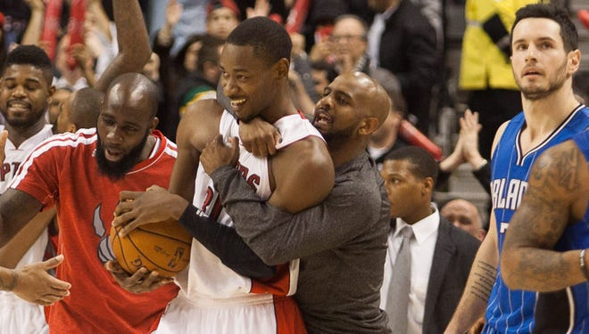 Terrence Ross, center, with basketball, is hugged by Raptors teammates after Friday's 93-90 win.