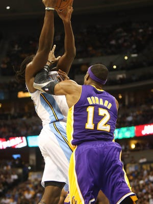 Denver Nuggets forward Kenneth Faried (left) is fouled by Los Angeles Lakers center Dwight Howard (12) during the second half at the Pepsi Center.