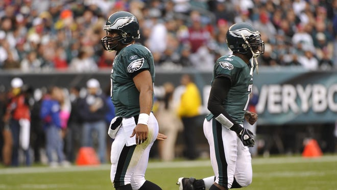 Donovan McNabb (left) and Michael Vick cross paths in a 2009 game.