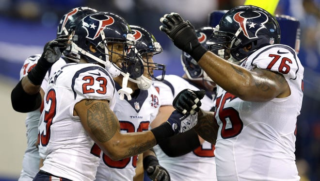 Houston Texans' Arian Foster (23) celebrates with his teammates following a 13-yard touchdown run against the Colts.