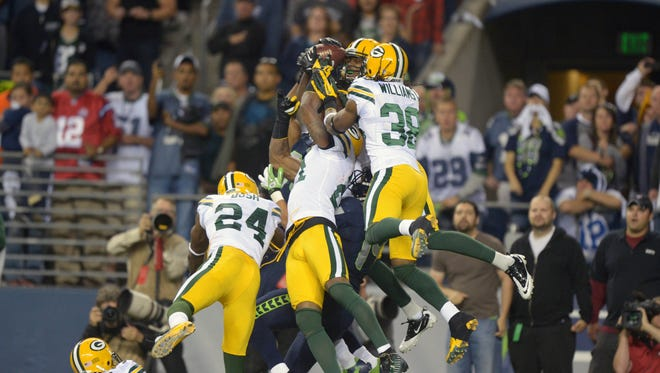 Seattle Seahawks receiver Golden Tate (81) catches a 24-yard touchdown pass as Green Bay Packers players Sam Shields (37), and Jarrett Bush (24), and Charles Woodson (21) and Jarrett Williams (38) defend on the final play at CenturyLink Field