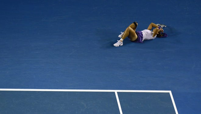 China's Li Na reacts after falling during the women's singles final against Belarus's Victoria Azarenka on day 13 of the Australian Open tennis tournament in Melbourne on January 26, 2013.