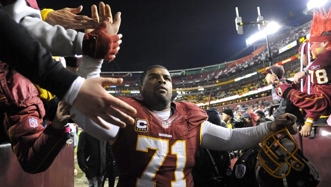 Redskins offensive tackle Trent Williams (71) receives congratulations from Redskin fans after they defeated the Dallas Cowboys 28-18 during their NFL football game, Sunday, Dec. 30, 2012, in Landover, Md. (AP Photo/Richard Lipski) ORG XMIT: OTKRL05