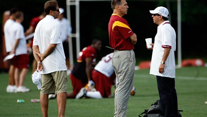 Washington Redskins Head Coach Jim Zorn (C) talks with owner Daniel Snyder (R) as Executive Vice President for Football Operations Vinny Cerrato (L) looks on during the first day of training camp July 30, 2009.