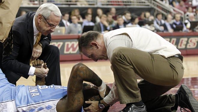 A trainer and North Carolina Tar Heels head coach Roy Williams (left) holds the hand of guard P.J. Hairston (15) after he was injured during the first half against the Boston College Eagles at Conte Forum.