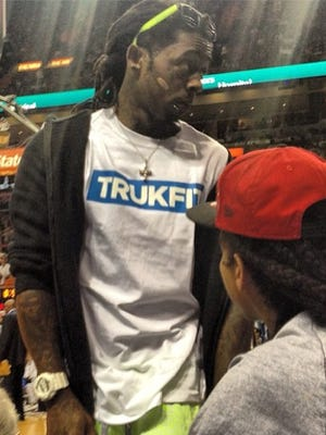 Lil Wayne stands up before leaving Sunday's Heat-Lakers game.