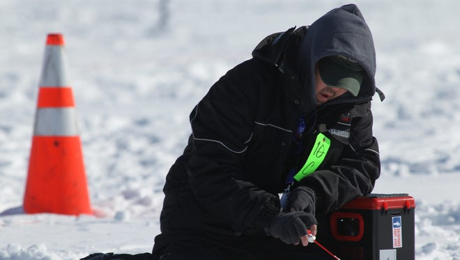 A competitor from the Mongolian team concentrates as he fishes during the World Ice Fishing Championship on the Eau Pleine Reservoir near Mosinee, Wis.