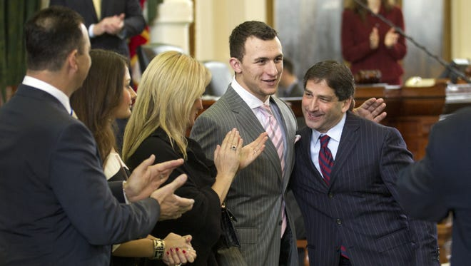 Johnny Manziel, Texas A&M Heisman Trophy-winning quarterback, is congratulated by Texas Sen. Kevin Eltife at the Senate Chamber at the Capitol in Austin, Tex., on Feb. 6.