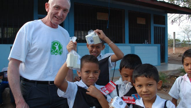 This photo shows children in Honduras showing their recycled hotel soap products with Terry Dunbar, general manager of the Hyatt Regency Jersey City in New Jersey.