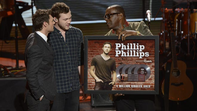 "AMERICAN IDOL: Phillip Phillips receives a plaque signifying his quadruple platinum single ""Home""  on AMERICAN IDOL Thursday, March 14 on FOX.  L-R: Ryan Seacrest, Phillip Phillips and Randy Jackson."