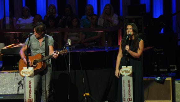 Keith Urban (L) and Kree Harrison play the Grand Ole Opry in Nashville, Tenn., June 4, 2013.