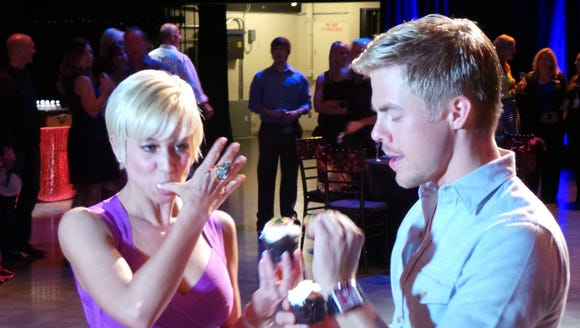 Kellie Pickler (L) and Derek Hough eat cupcakes backstage at the Grand Ole Opry.