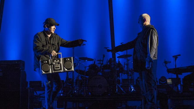Actor John Cusack passes the boom box to Peter Gabriel during his perfomance of the album 'So' at Hollywood Bowl on Saturday.