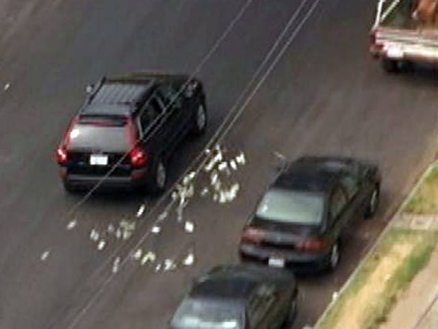 Bank robbers toss cash during chase through L A