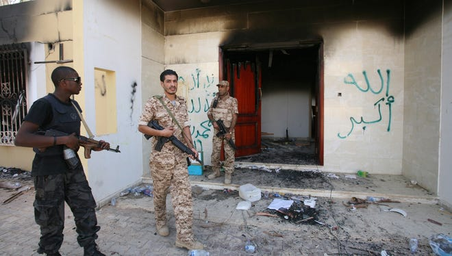 Libyan military guards check one of the burned-out buildings at the U.S. Consulate complex in Benghazi, Libya, three days after the Sept. 11 assault that killed U.S. Ambassador Christopher Stevens and three other Americans, including two guards at a CIA base about a mile from the consulate.