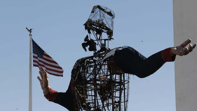 The burned remains of Big Tex stand at the State Fair of Texas on Oct. 19 in Dallas. Fire destroyed Big Tex on Friday, leaving behind little more than the metal frame of the 52-foot-tall metal-and-fabric cowboy that was an icon of the State Fair of Texas.