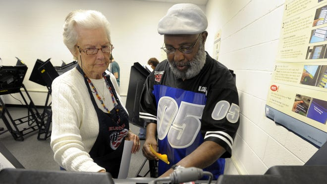 Frances High helps Manuel Sanders of Wilson, N.C., at an electronic voting booth.