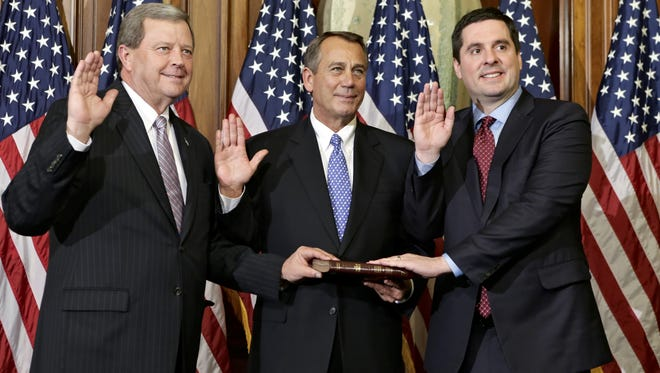 House Speaker John Boehner, center, re-enacts the swearing-in of Reps. Tom Latham, R-Iowa, left, and Rep. Devin Nunes, R-Calif. This is Latham's 10th term and Nunes' sixth term in Congress.