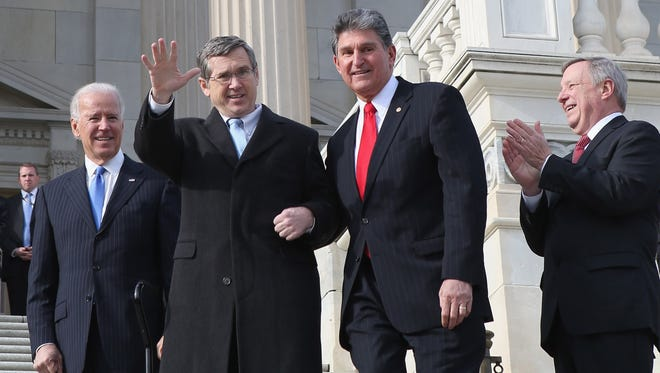 Sen. Mark Kirk, R-Ill., waves to the crowd as he makes his way up the Capitol steps.
