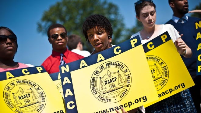 NAACP members hold signs in front of the Supreme Court, which struck down a key part of the landmark Voting Rights Act.