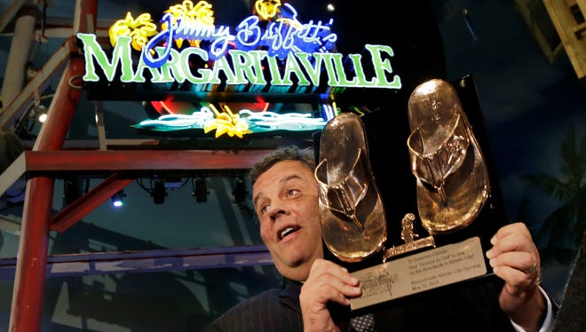 New Jersey Gov. Chris Christie holds up a pair of bronzed beach shoes at a restaurant opening inside Resorts Casino Hotel in Atlantic City.