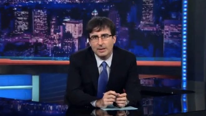 John Oliver sits behind the desk on 'The Daily Show.'