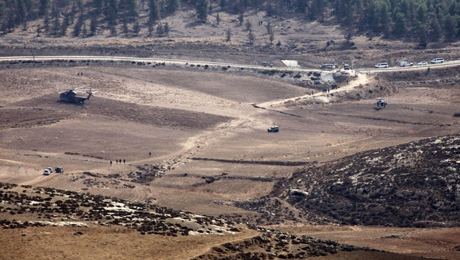 Israeli Army vehicles and helicopters are seen in an open area as they search for the remains of a drone in the Negev southern Israel on Saturday.