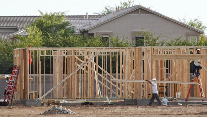 Workers frame the first home in a new  community in Gilbert, Ariz.