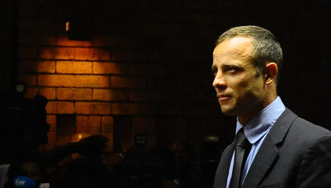 Olympic athlete Oscar Pistorius stands in court following his bail hearing in Pretoria, South Africa, Tuesday, Feb. 19, 2013.  Pistorius fired into the door of a small bathroom where his girlfriend was cowering after a shouting match on Valentine's Day, hitting her three times, a South African prosecutor said Tuesday as he accused the sports icon of premeditated murder.  The magistrate ruled that Pistorius faces the harshest bail requirements available in South African law, but did not elaborate before a break was called in the session. (AP Photo) ORG XMIT: XDF110