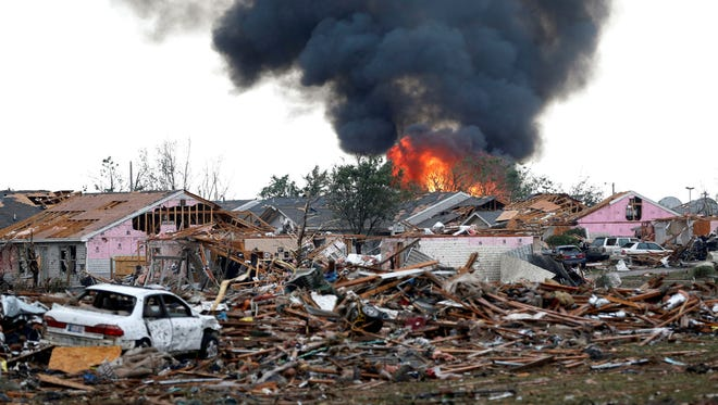 A fire burns in the Tower Plaza Addition in Moore, Okla., following a tornado on Monday.