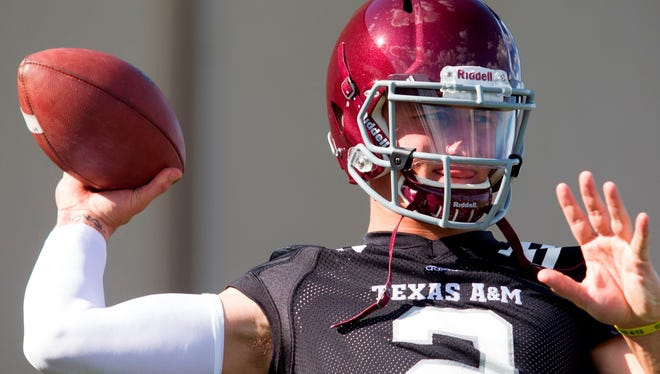 Texas A&M quarterback and Heisman Trophy winner Johnny Manziel throws during football practice, Monday, Aug. 5.