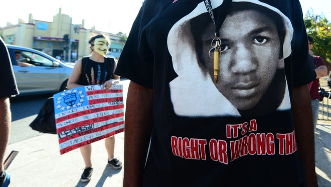 A man wears a single bullet around his neck over his Trayvon T-shirt as people hold placards and shout slogans during a rally in Los Angeles in the aftermath of George Zimmerman's acquittal in the shooting death of Florida teen Trayvon Martin,  on July 15 in California, where local civil rights activists and other leaders urged participants to remain peaceful as they express frustration with the trial's outcome.