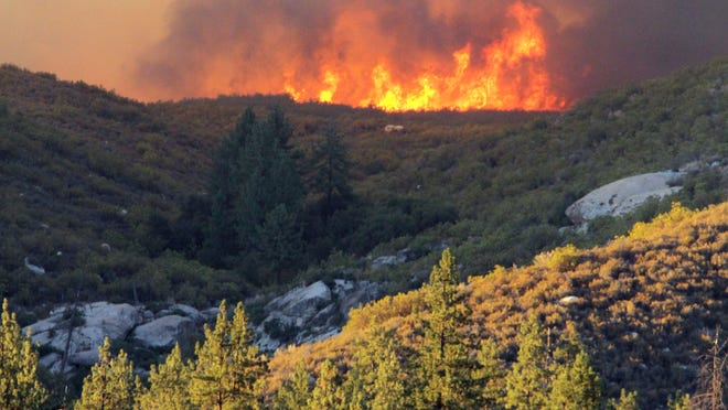 Wildfire burns over a ridgeline near the communities of Idyllwild, Mountain Center and Garner Valley, Calif., on Monday.
