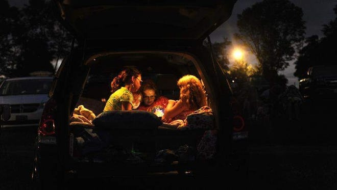 Theresa Evans, daughters Serena, 6, and Olivia, 10, and friend Sarah Dudley, 10, play a game in the back of a van July 7, 2013, at Hull's Drive-In in Lexington, Va.