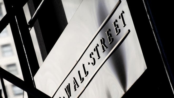 A sign for Wall Street is shown outside the New York Stock Exchange. Stocks were trading lower Friday.