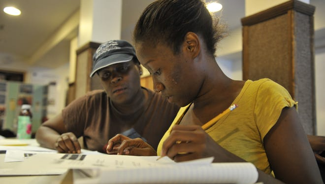 Loretta Kennedy, left, and Shanae Williams, work problems while preparing at Southeast Ministry GED-Adult Basic Education class to take the GED high school equivalency test, which is being revamped for 2014.