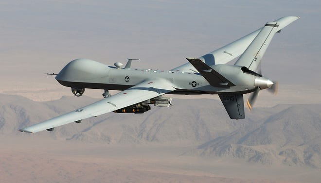 An MQ-9 Reaper, armed with GBU-12 Paveway II laser guided munitions and AGM-114 Hellfire missiles, piloted by Col. Lex Turner, flies over southern Afghanistan.
