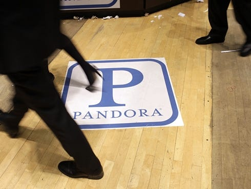 Traders on the floor of the New York Stock Exchange walk over insignia for Pandora Media, the online-radio company, on its first day of trading on June 15, 2011.