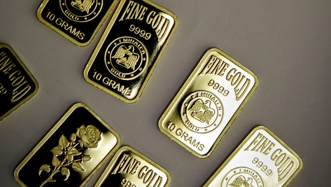 """Gold bars with a purity of 999.9 have been pressed and stamped with the  """"Emirates Gold"""" company logo in Dubai, United Arab Emirates."""