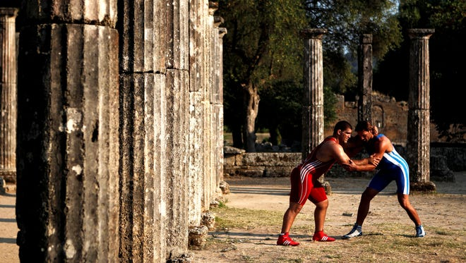 Greece's Ioannis Arzoumanidis, left, and Greece's Georgios Koutsioubas, a world champion in men's under 21 Greco-Roman, perform to promote their sport at Palaestra in ancient Olympia, on Sunday.