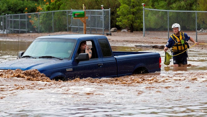A man and a woman sit in a truck on Tomahawk Road that was flooded by monsoon rain waters in Apache Junction, Ariz., on Sunday, July 21, 2013. The Mesa Fire Department was able to get the two out of the vehicle safely.
