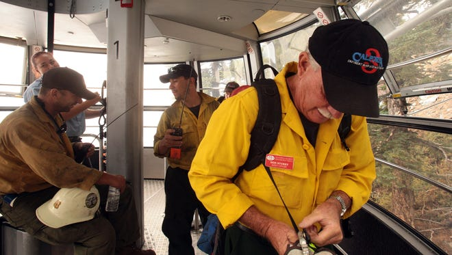 California Incident Management Team 3 safety officer Don Stukey prepares his individual equipment before offloading a tram car at the Palm Springs Aerial Tramway's Mountain Station on Sunday, July 21, 2013.